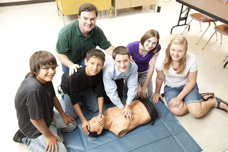CPR class with resuscitation dummy, indicating the type of training available from First Aid Matters.